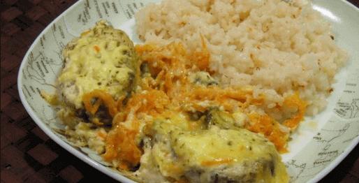 Риба хек с ориз и моркови в чиния на кафява маса