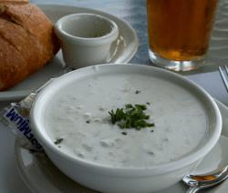 Млечна рибена супа с бяла риба и зеленчуци в бяла купа и отзад хляб
